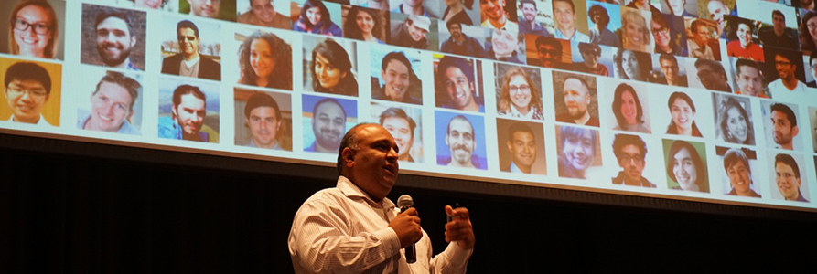 Professor Rayid Ghani speaking in front of a screen with a photo montage