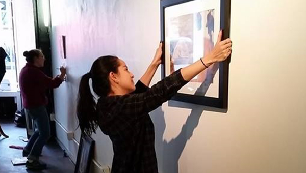 A student hangs a piece of art on the wall at Future Tenant art space