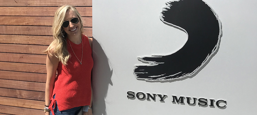 An alumna poses by a Sony Music sign