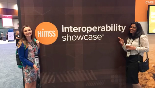 Students stand in front of a sign reading HIMSS Interoperability Showcase