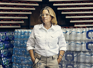 Carmen Yulin Cruz in front of palettes of water