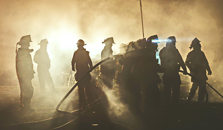image of firefighters backlit at night