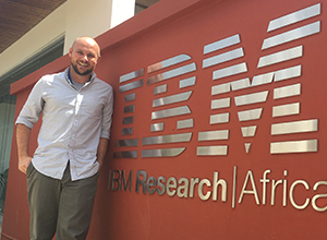 Skyler Speakman standing in front of IBM sign at IBM Africa