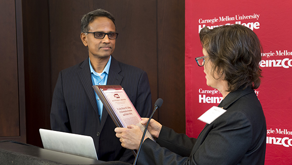 Krishnan is presented with a plaque during George D Smith Prize Ceremony