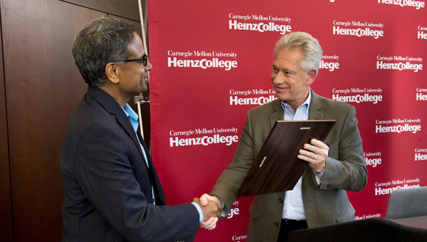 Krishnan is given a plaque during George D Smith Prize Ceremony