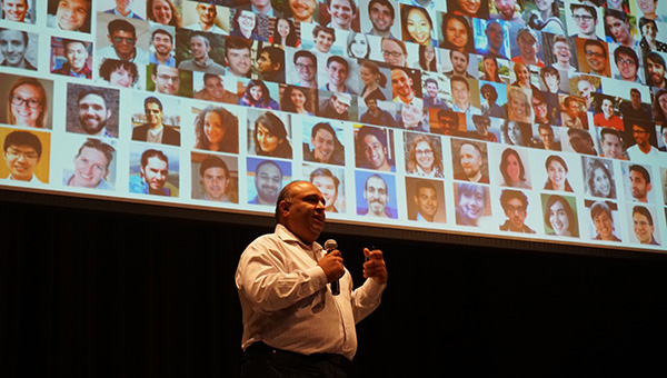 Professor Rayid Ghani speaking in front of a mosaic of faces